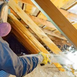 person spraying insulation into attic while wearing mask