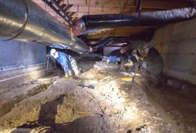 Eastside technicians in a crawl space applying insulation.
