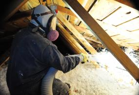 Technician from Eastside spraying insulation in an attic.