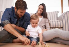 Father, mother, and baby sitting on the floor of their home playing with blocks.